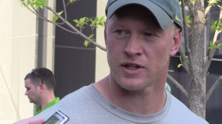 Scott Frost talks to reports after practice